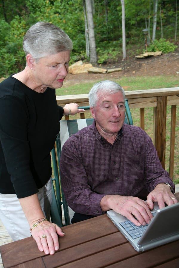 Couples aînés heureux sur l'ordinateur photographie stock libre de droits