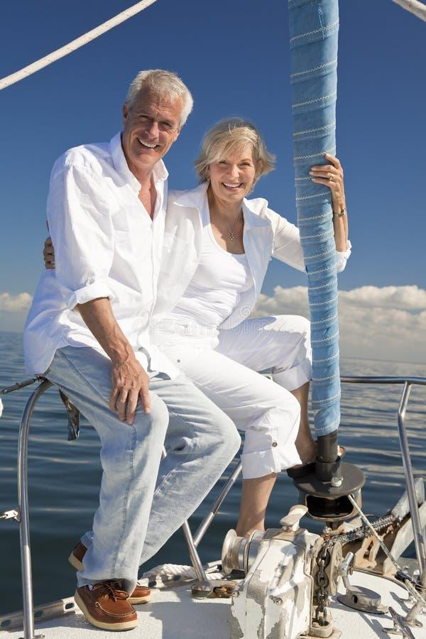 Couples aînés heureux sur un bateau à voile photo libre de droits