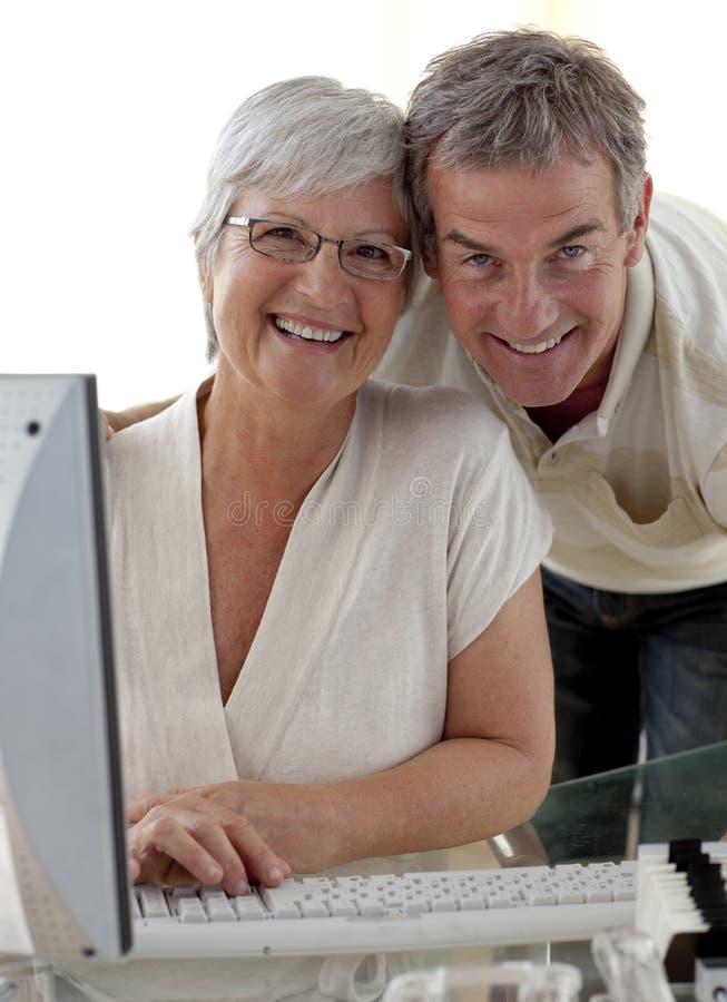 Couples aînés heureux utilisant un ordinateur photos stock