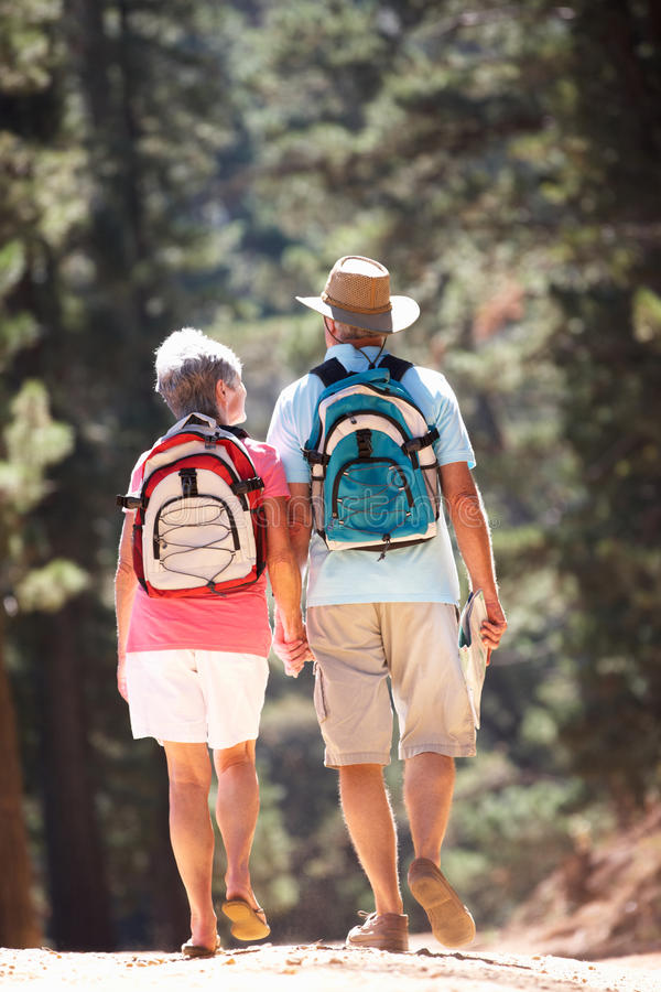 Couples aînés marchant le long d'une route de campagne photos stock