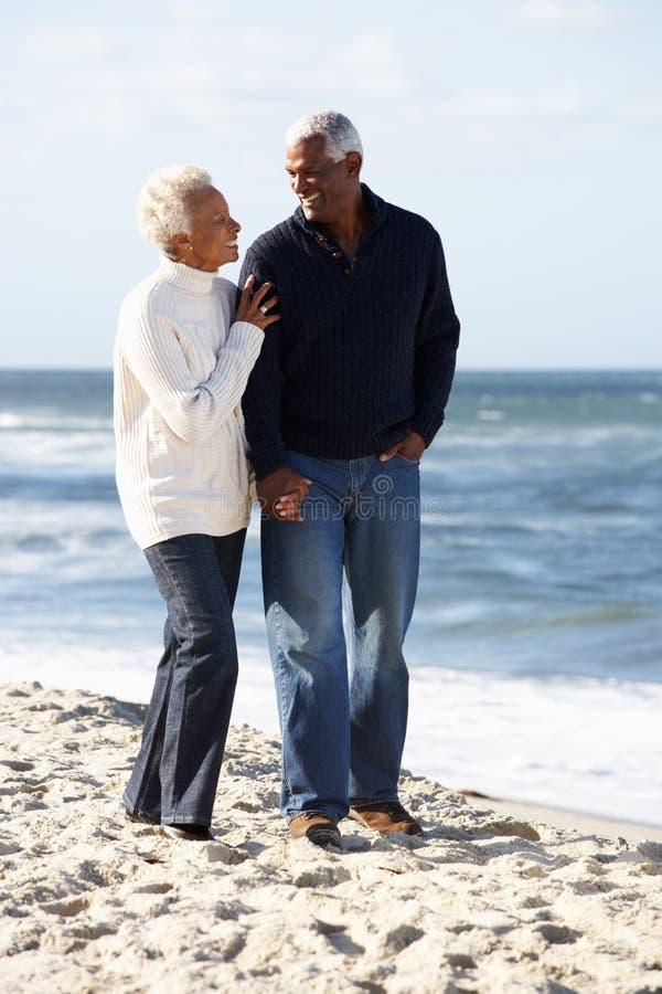 Couples aînés marchant le long de la plage ensemble photo stock