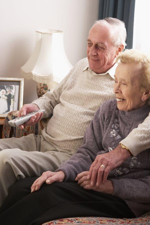 Couples aînés regardant la TV à la maison photos libres de droits