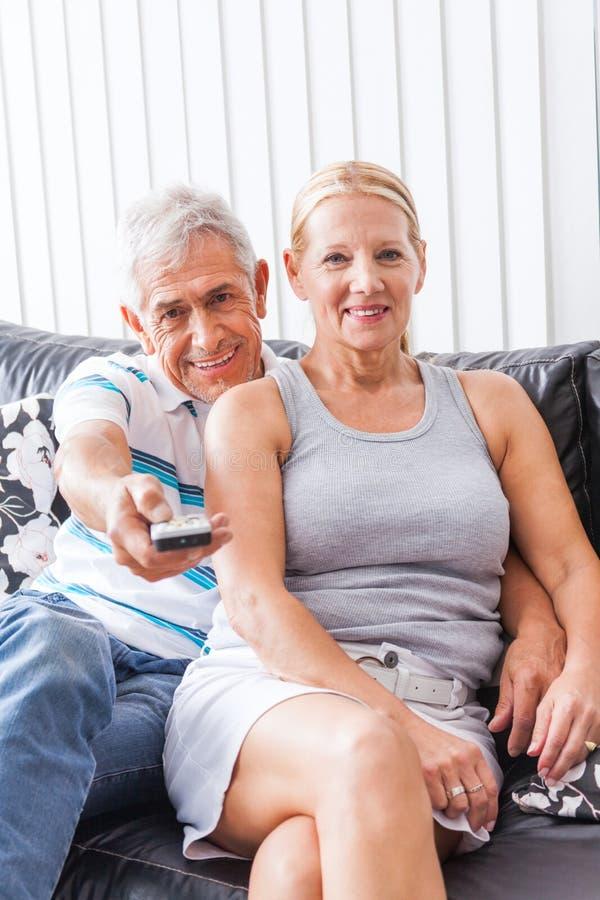 Couples aînés regardant la TV images libres de droits