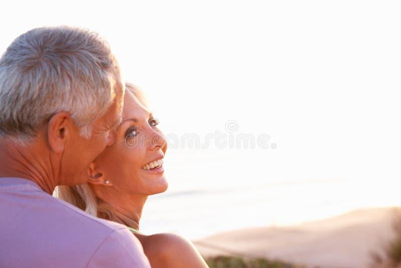Couples aînés romantiques dans l'amour au coucher du soleil image libre de droits