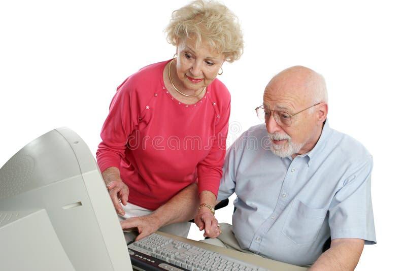 Couples aînés sur l'ordinateur images stock