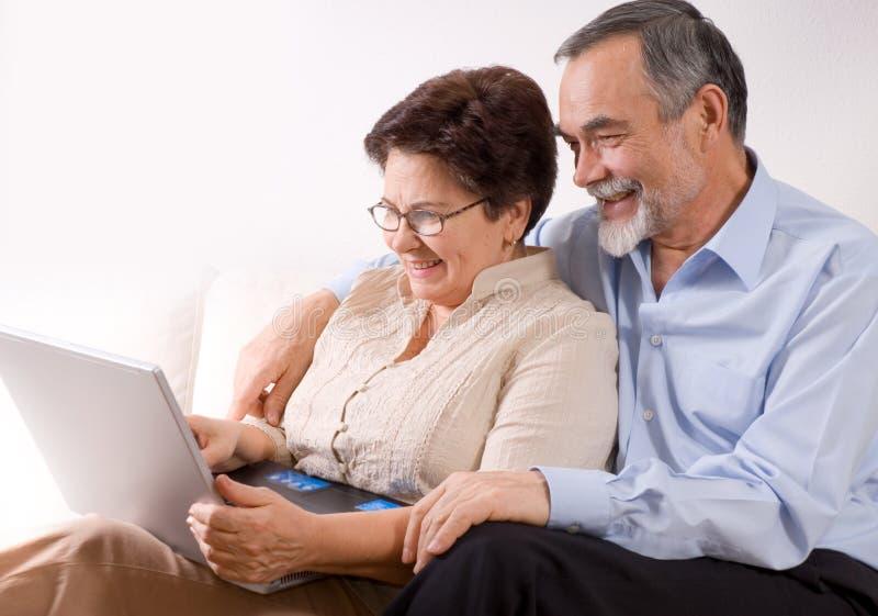 Couples aînés sur l'ordinateur portatif images libres de droits