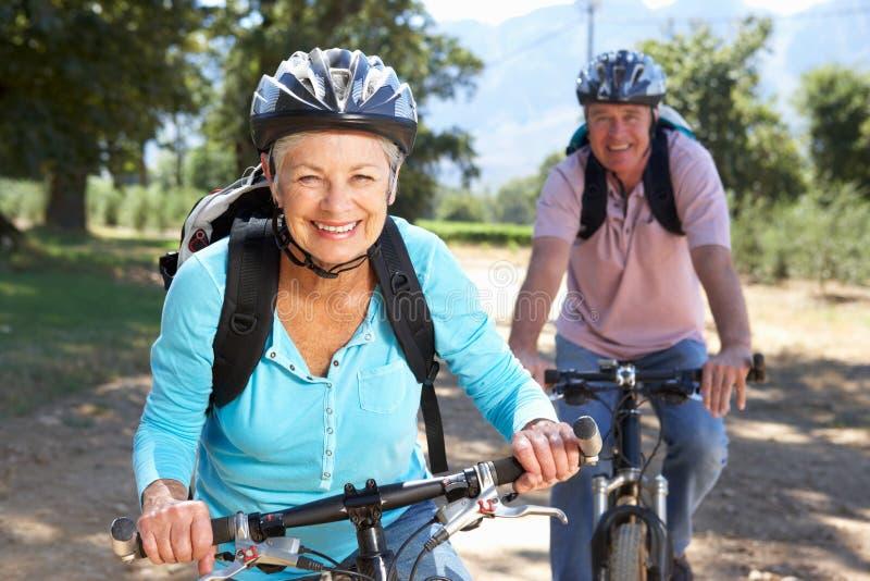 Couples aînés sur la conduite de vélo de pays photo stock