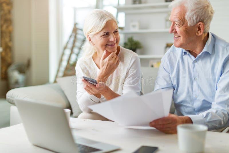 Couples aînés utilisant l'ordinateur portable à la maison photo stock
