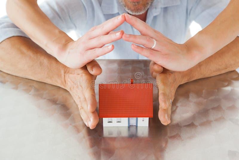 Couples abritant la maison miniature avec des mains photos stock