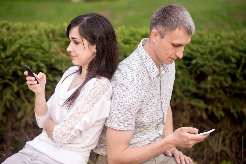 Couples absorbés dans la communication de téléphone photo stock