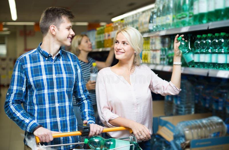 Couples achetant l'eau minérale photo stock