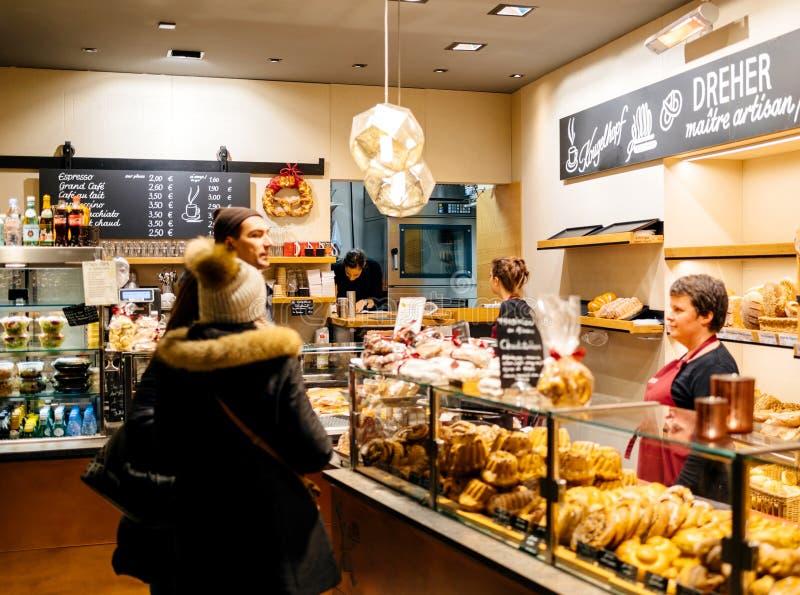 Couples achetant les gâteaux et le pain fraîchement cuits au four de kougelhof dans un germe image stock