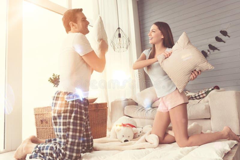 Couples actifs d'amusement ayant un combat d'oreiller images libres de droits
