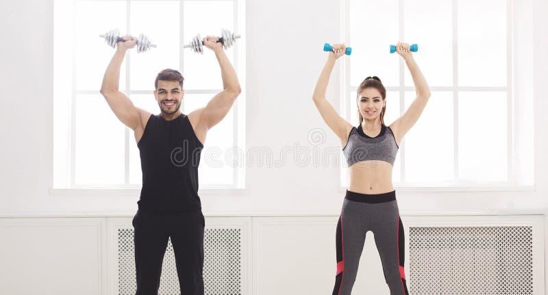 Couples actifs pompant leurs mains avec des haltères dans le studio photo stock