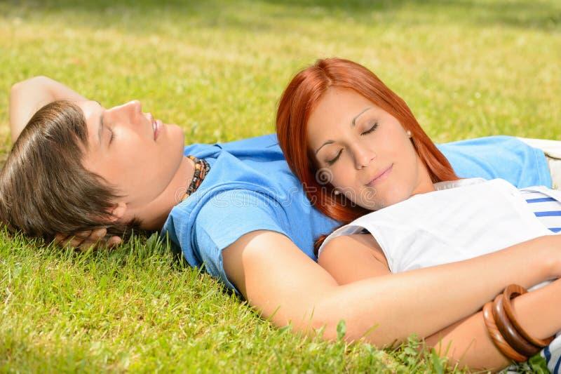 Couples adolescents détendant sur les yeux fermés d'herbe photographie stock libre de droits