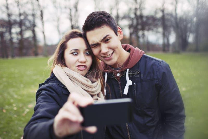 Couples adolescents drôles se photographiant images stock