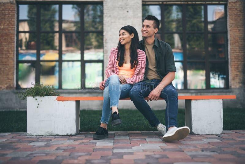 Couples adorables étreignant sur le banc et semblant heureux image libre de droits