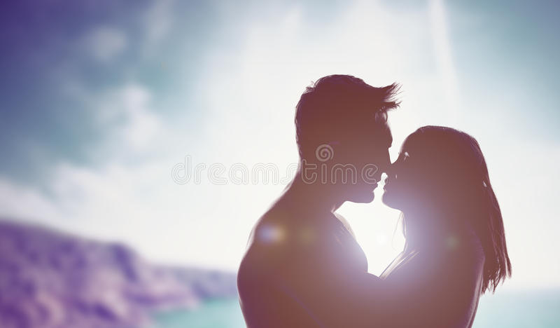 Couples affectueux éclairés à contre-jour par un soleil lumineux image libre de droits