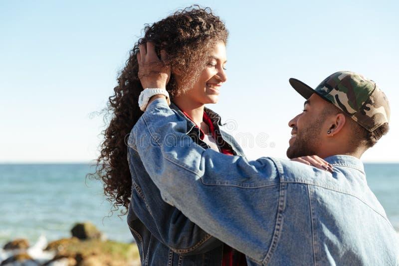 Couples affectueux africains heureux marchant dehors à la plage image libre de droits
