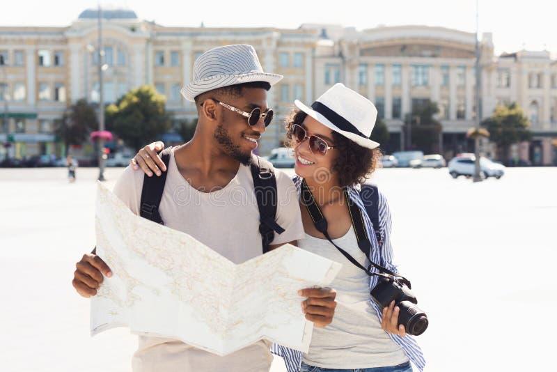 Couples affectueux d'afro-américain voyageant et lisant la carte dans la ville photo libre de droits