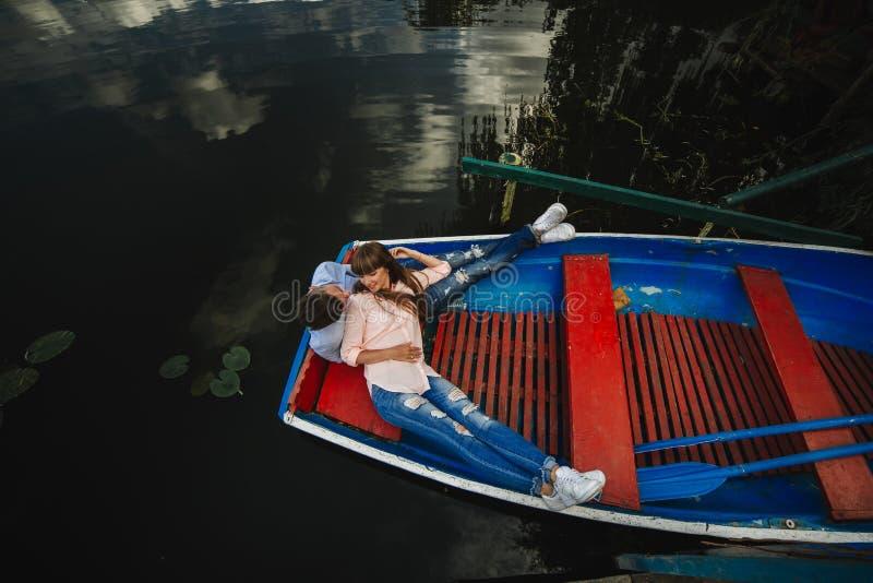 Couples affectueux dans le bateau Vue sup?rieure de beaux jeunes couples embrassant et souriant tout en se situant dans le bateau image stock