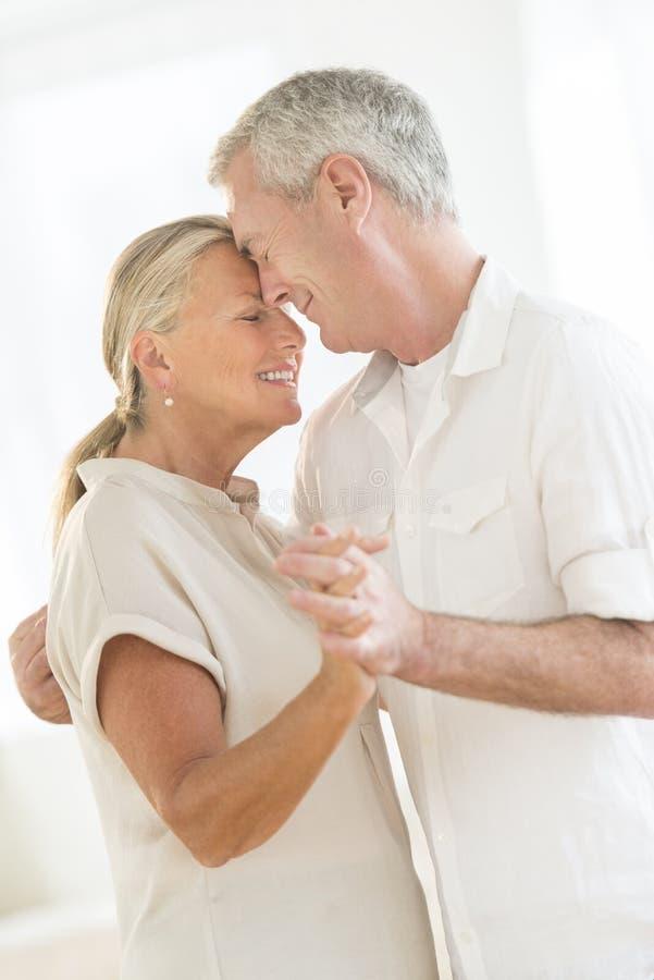 Couples affectueux dansant à la maison images libres de droits