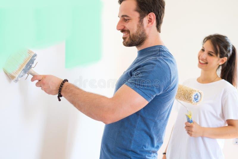 Couples affectueux de sourire faisant les rénovations à la maison ensemble photographie stock libre de droits