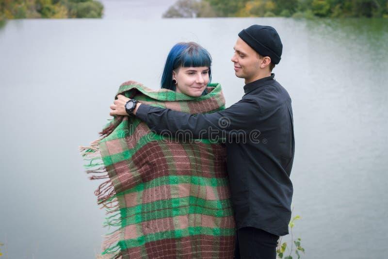 Couples affectueux enveloppés dans le plaid se reposant sur la montagne dehors sur le coucher du soleil Vue de rivière Homme et f photo libre de droits