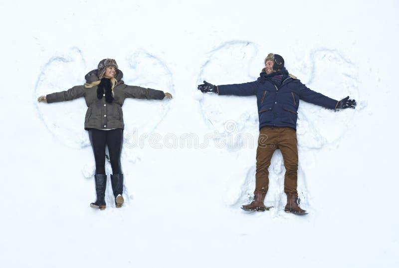 Couples affectueux faisant l'ange de neige photo libre de droits
