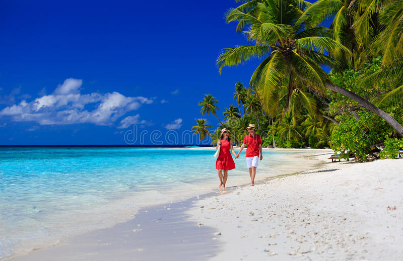 Couples affectueux heureux marchant sur la plage d'été photo stock