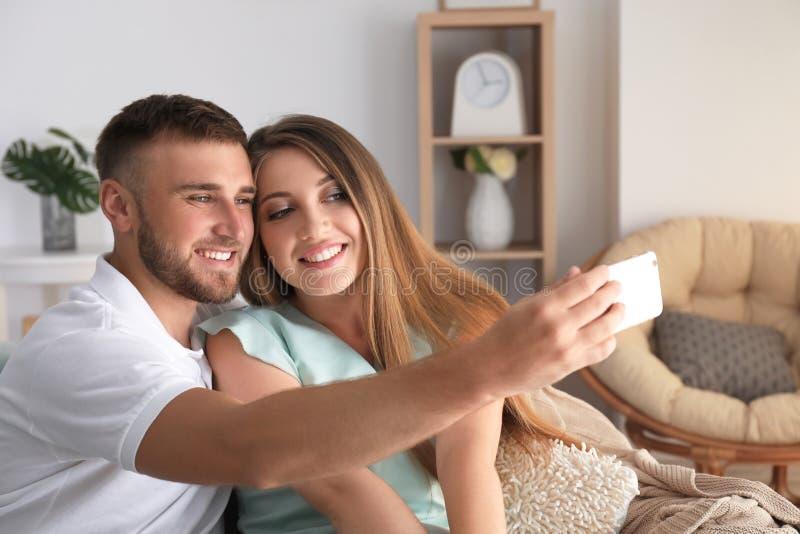 Couples affectueux heureux prenant le selfie à la maison photo stock