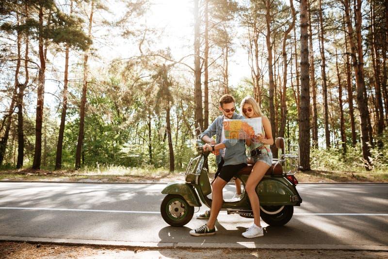 Couples affectueux heureux tenant la carte dehors près du scooter photographie stock libre de droits