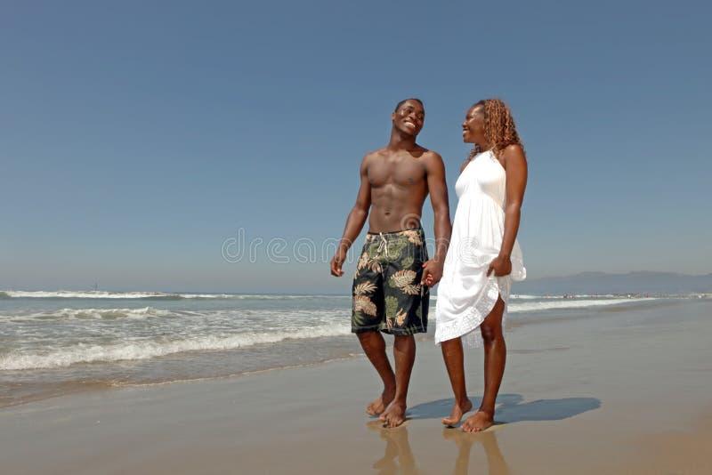 Couples affectueux jouant le long de la plage photographie stock libre de droits