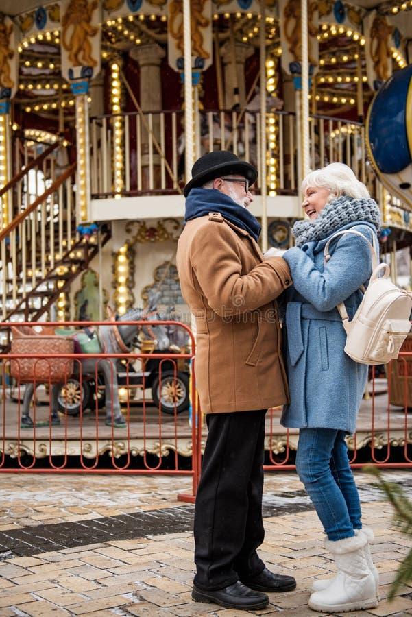 Couples affectueux mûrs heureux tenant des mains sur la rue images stock