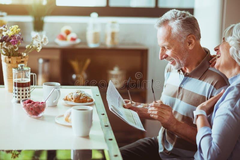 Couples affectueux positifs appréciant leur petit déjeuner dans la cuisine photo stock