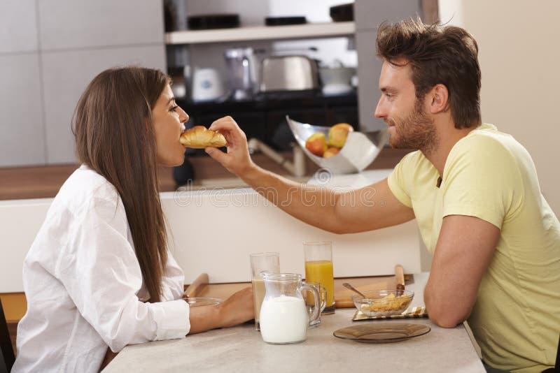 Couples affectueux prenant le petit déjeuner ensemble images libres de droits