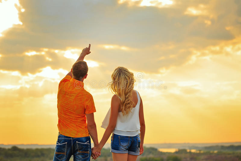 Couples affectueux regardant le ciel le coucher du soleil image stock