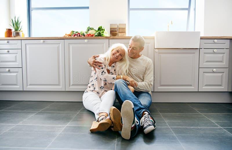Couples affectueux se reposant sur le plancher de cuisine image stock