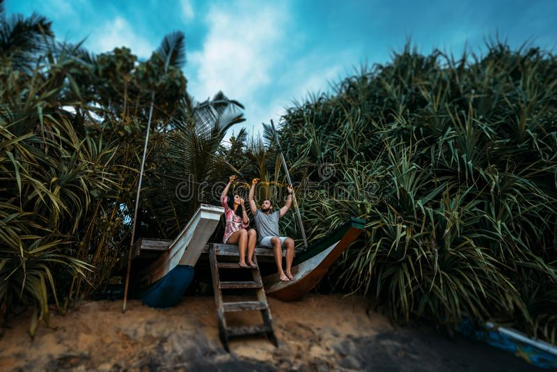 Couples affectueux sur la plage avec la guirlande photographie stock libre de droits