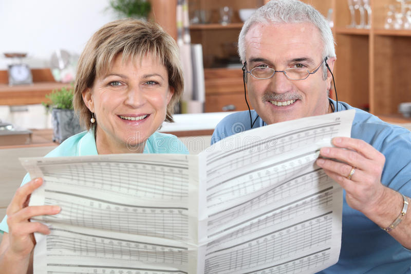 Couples affichant un journal photographie stock libre de droits