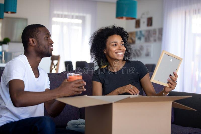 Couples africains heureux ayant l'amusement déballant des boîtes dans le salon images libres de droits
