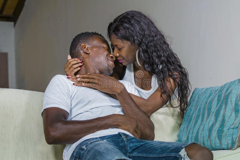 Couples afro-américains noirs heureux caressant à la maison le sourire de divan de sofa de salon gai ayant l'amusement décontract images libres de droits