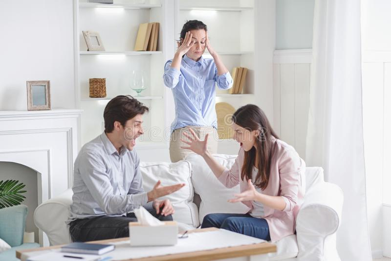 Couples agressifs fâchés se disputant à la session de thérapie image stock