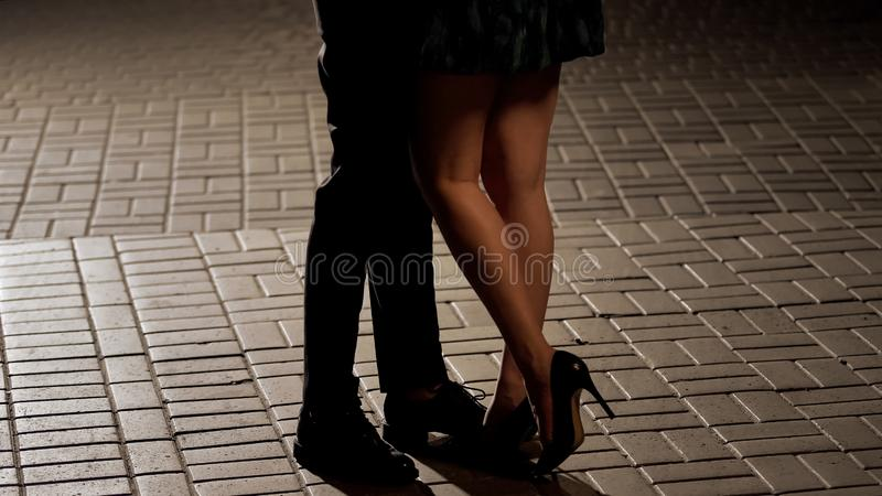 Couples aimants étreignant et embrassant dans la rue, vue des jambes, relations image stock