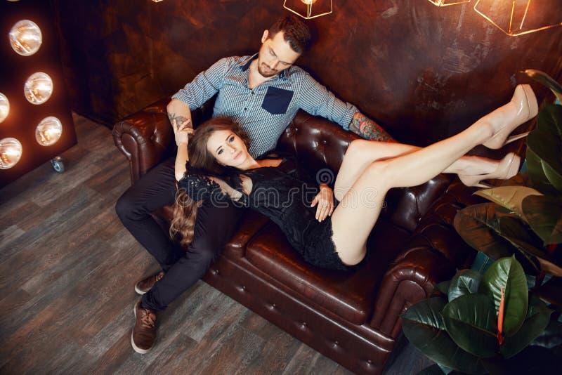 Couples aimants étreignant sur le divan contre les lumières lumineuses des lampes La passion et la tendresse, l'homme et la femme photographie stock