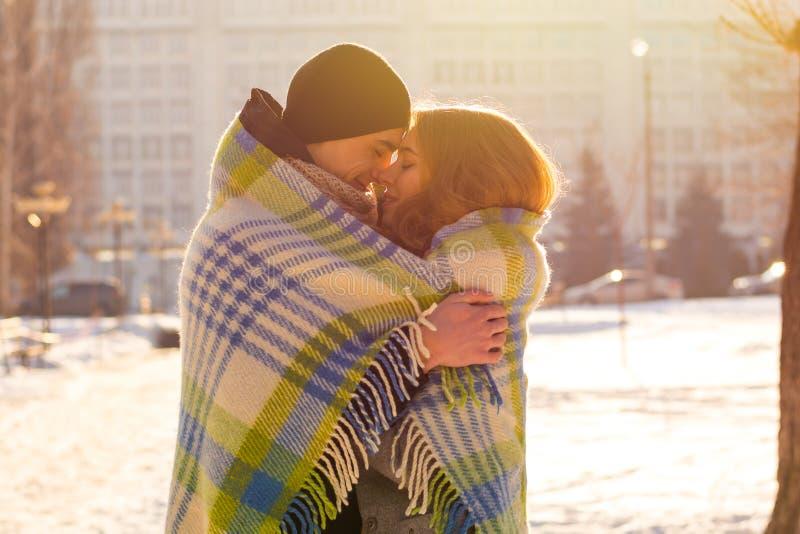 Couples aimants dans une couverture en hiver Le type étreint une fille sur la rue en hiver photos stock