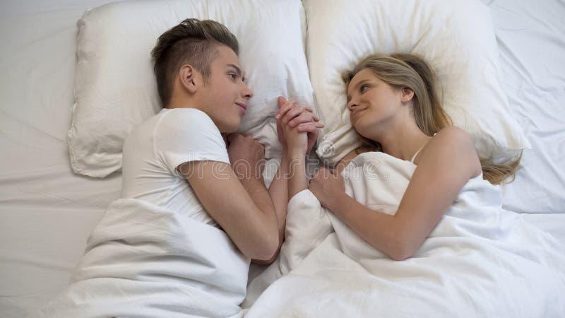 Couples aimants des adolescents se situant dans le lit, tenant tendrement des mains, moment romantique photographie stock
