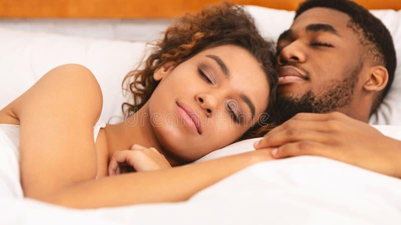 Couples aimants dormant le lit et en étreignant photographie stock
