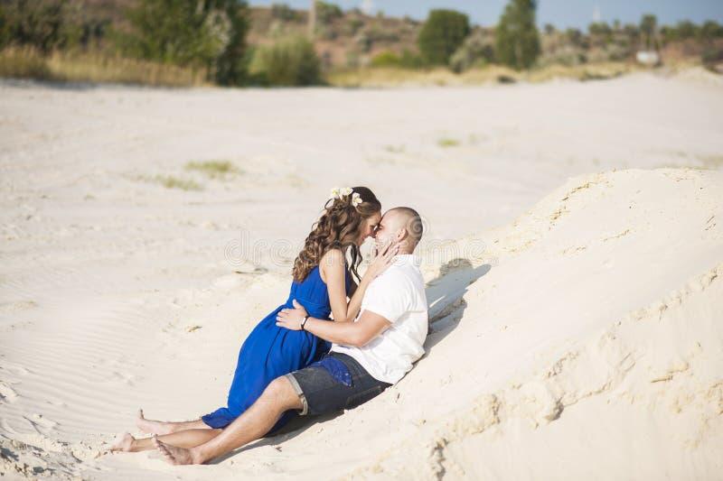 Couples aimants sur la plage dans étreindre de sable Le concept de l'amour et une date en mer photographie stock libre de droits