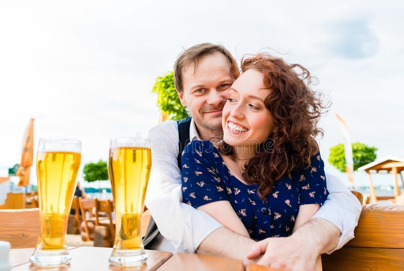Couples amoureux caressant dans le jardin de bière images stock